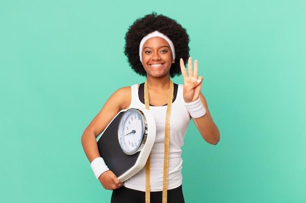 Afro-frau lächelt und sieht freundlich aus, zeigt nummer drei oder dritte mit der hand nach vorne und zählt das diätkonzept herunter
