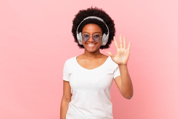 Afro-frau lächelt und sieht freundlich aus, zeigt nummer fünf oder fünf mit der hand nach vorne und zählt herunter. musikkonzept