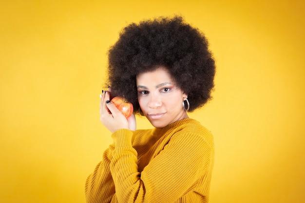 Afro-frau mit einem apfel in den händen auf gelbem hintergrund