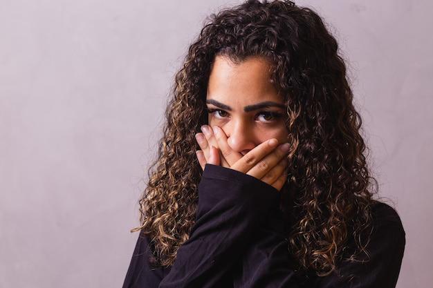 Afro-frau mit hand im mund, konzept von missbrauch, feminizid, rassismus und vorurteilen