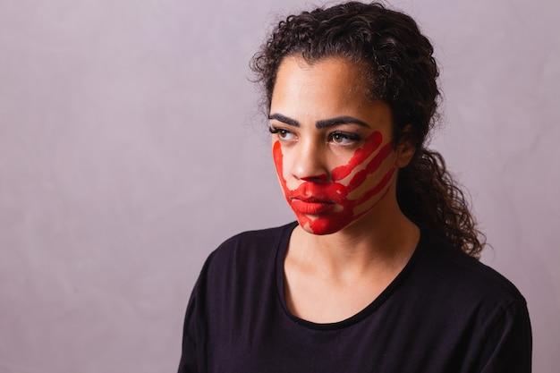 Afro-frau mit handabdruck auf dem mund zugunsten des bewusstseins für feminizid. häusliche gewalt