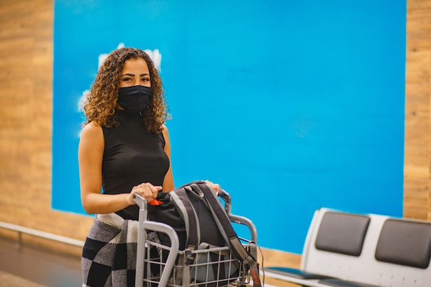 Afro frau mit koffern am flughafen. frau am flughafen, der in der pandemie reist