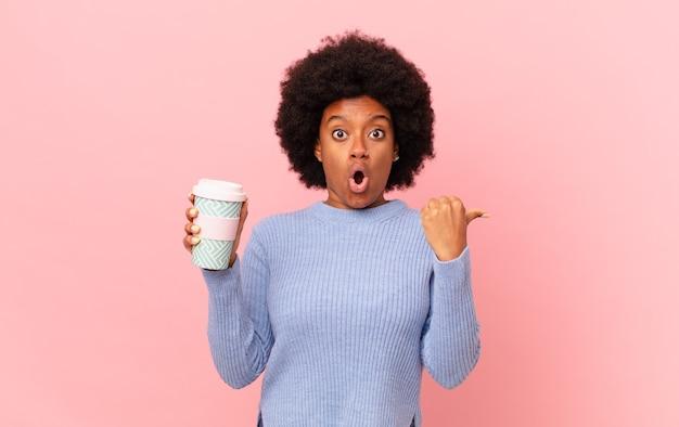 Afro-frau sieht ungläubig aus, zeigt auf das objekt an der seite und sagt wow, unglaublich. kaffeekonzept