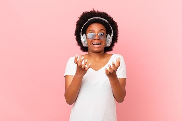 Afro-frau sieht verzweifelt und frustriert, gestresst, unglücklich und verärgert aus, schreit und schreit. musikkonzept