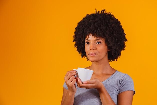 Afro-frau trinkt tee auf gelb