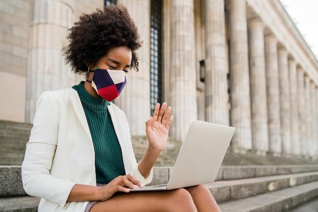 Afro-geschäftsfrau, die schutzmaske trägt und einen videoanruf auf laptop beim sitzen auf treppen im freien hat. stadt- und geschäftskonzept.