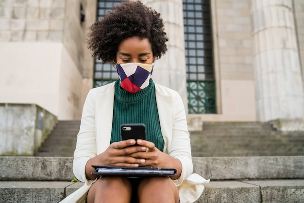 Afro-geschäftsfrau, die schutzmaske trägt und ihr handy benutzt, während sie auf treppen draußen an der straße sitzt. geschäfts- und stadtkonzept.