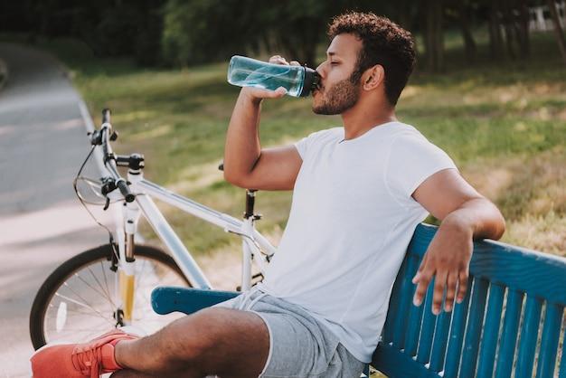 Afro guy drinks water auf park bench nahe bei fahrrad