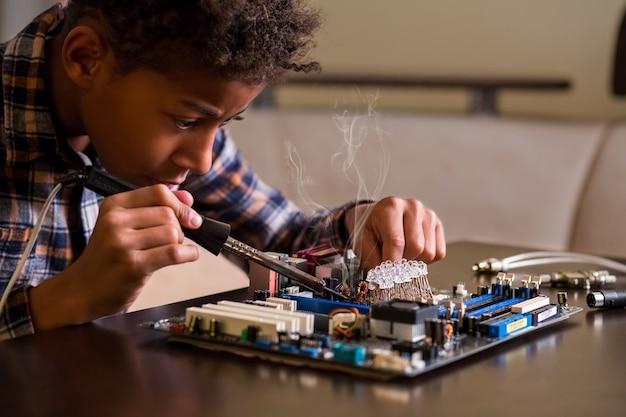 Afro-junge, der das motherboard repariert.
