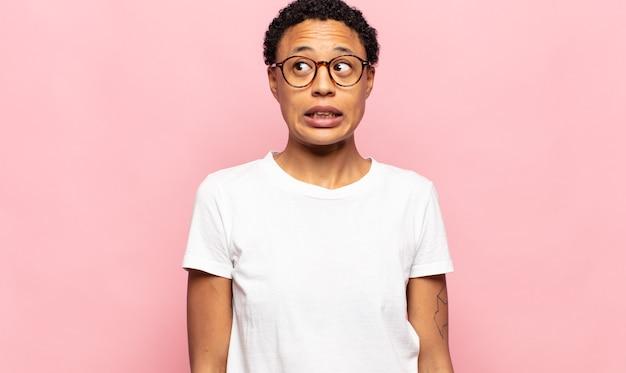 Afro junge frau, die besorgt, gestresst, ängstlich und ängstlich aussieht, in panik gerät und zähne zusammenbeißt