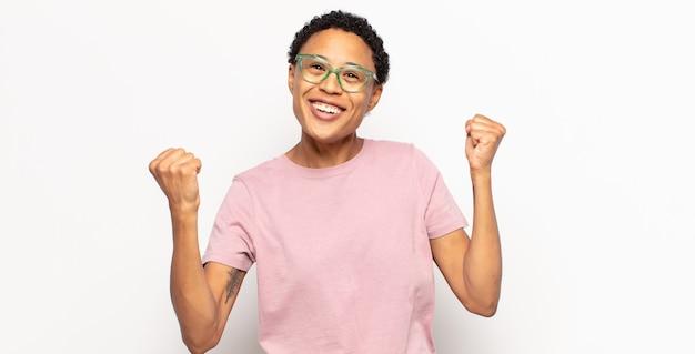Afro junge frau feiert einen unglaublichen erfolg wie ein gewinner, sieht aufgeregt und glücklich aus zu sagen, nimm das!