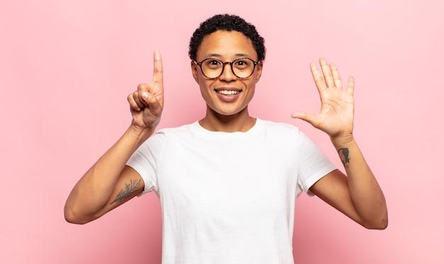Afro junge frau lächelt und sieht freundlich aus, zeigt nummer sechs oder sechste mit der hand nach vorne, countdown