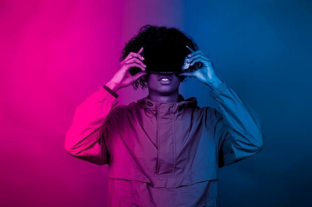 Afro-junge mit vr-brille. ein junger afro, der in die virtuelle realität eingetaucht ist, macht bewegungen mit seinen händen. blaues und rotes licht fällt auf einen jungen.