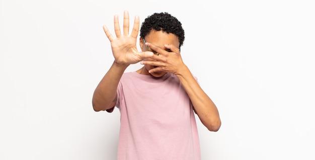 Afro junge schwarze frau, die gesicht mit hand bedeckt und andere hand nach vorne legt, um kamera zu stoppen, fotos oder bilder ablehnend