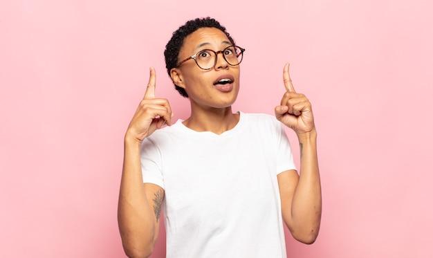 Afro junge schwarze frau, die schockiert, erstaunt und mit offenem mund aussieht und mit beiden händen nach oben zeigt, um den raum zu kopieren