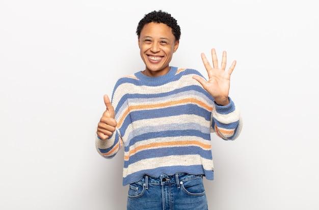 Afro junge schwarze frau lächelnd und freundlich aussehend, zeigt nummer sechs oder sechste mit der hand nach vorne, countdown