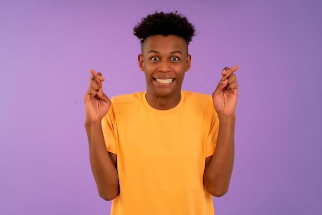 Afro junger mann, der ihre finger kreuzt und viel glück wünscht.