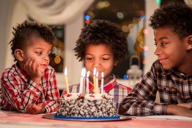 Afro-jungs und geburtstagstorte drei kinder sitzen neben kuchen und wünschen sich heute abend geburtstagsfeier ...