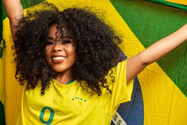 Afro-mädchen, das für brasilianische lieblingsmannschaft jubelt und nationalflagge in der gelben wand hält.