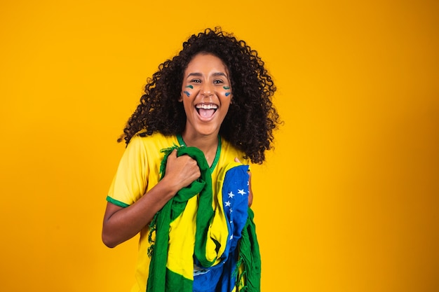 Afro-mädchen jubeln für das brasilianische lieblingsteam und halten die nationalflagge in gelbem hintergrund.