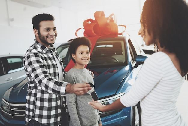Afro man präsentiert auto zu frau jubiläumsgeschenk.