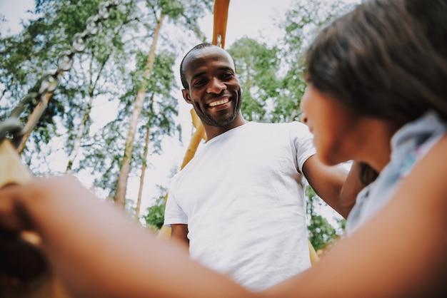 Afro man swinging mixed race daughter auf schaukel
