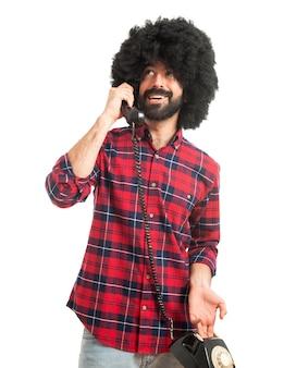 Afro mann im gespräch mit vintage telefon