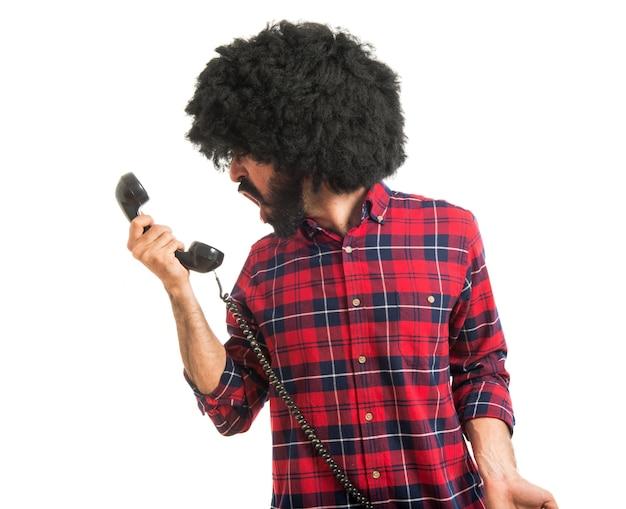 Afro mann schreit durch vintage telefon