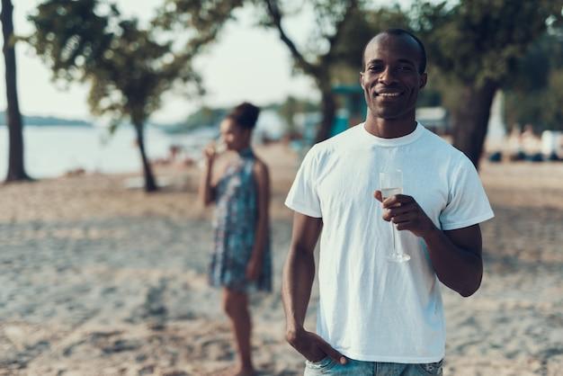 Afro-paar trinkt champagner auf sandy river beach.