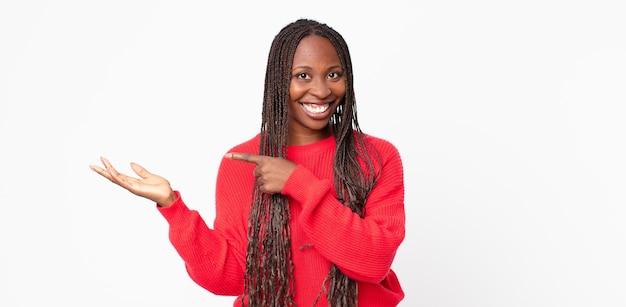 Afro-schwarze erwachsene frau, die fröhlich lächelt und auf den seitlichen platz auf der handfläche zeigt, ein objekt zeigt oder annonciert