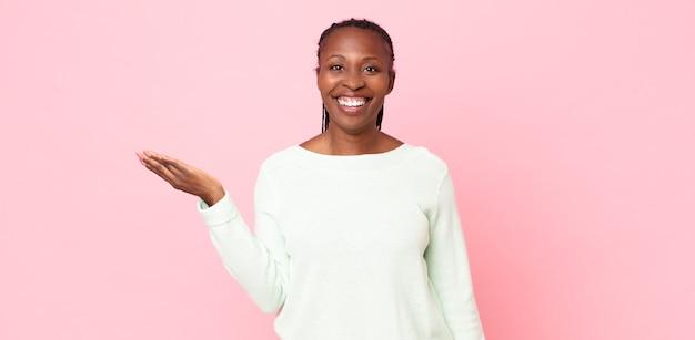 Afro-schwarze erwachsene frau, die sich glücklich, überrascht und fröhlich fühlt, mit positiver einstellung lächelt und eine lösung oder idee realisiert