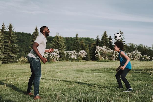Afro-sohn und vater spielen zusammen im ball auf natur