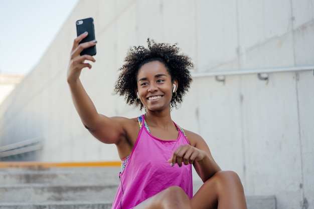 Afro sportliche frau, die ein selfie mit ihrem handy nimmt und sich nach dem training im freien entspannt