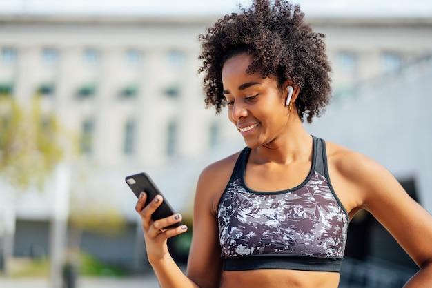 Afro sportliche frau, die ihr handy benutzt und sich nach dem training im freien entspannt