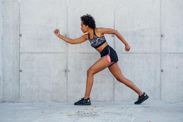 Afro sportliche frau läuft und macht übung im freien. sport und gesunder lebensstil konzept.