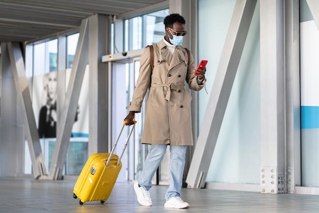 Afro tausendjähriger mann, der mit koffer im flughafen geht