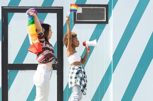Afro- und kaukasierinnen mit gay-pride-flagge und megaphon demonstrieren für gleichberechtigung