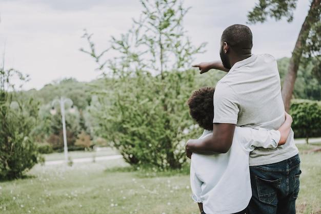 Afro-vater umarmt seinen afro-sohn und zeigt seine hand.