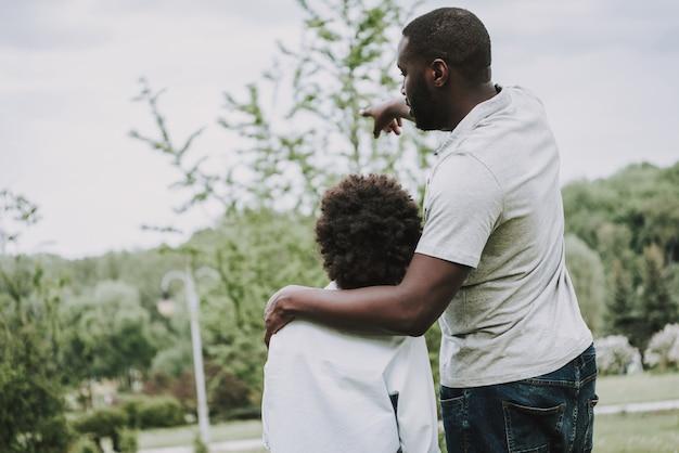 Afro vater umarmt seinen sohn und zeigt seine hand