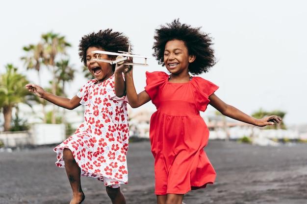 Afro-zwillingsschwestern, die am strand laufen, während sie mit holzspielzeugflugzeug spielen - jugendlebensstil und reisekonzept - hauptfokus auf rechtem kindergesicht