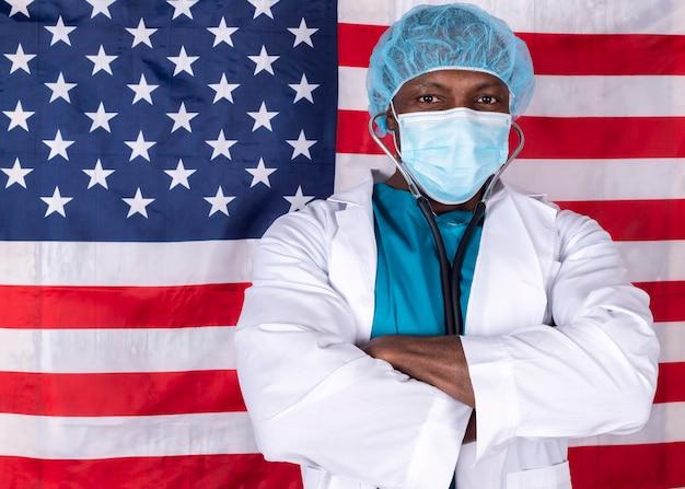 Afroamerikaner-arzt mit gekreuzter gesichtsmaske, usa-flagge