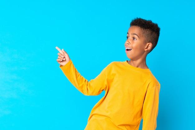 Afroamerikaner boyblue hintergrund überrascht und finger auf die seite zeigend