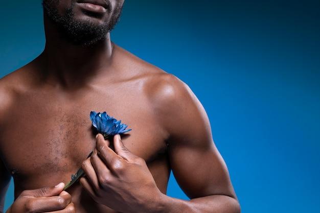 Afroamerikaner, der eine blaue blume hält