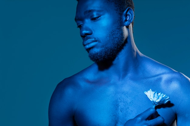 Afroamerikaner, der eine blume hält