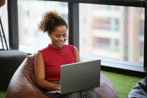 Afroamerikaner, der ihren laptop in der kaffeestube betrachtet