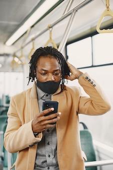 Afroamerikaner, der im stadtbus reitet. mann in einem braunen mantel. corona-virus-konzept.