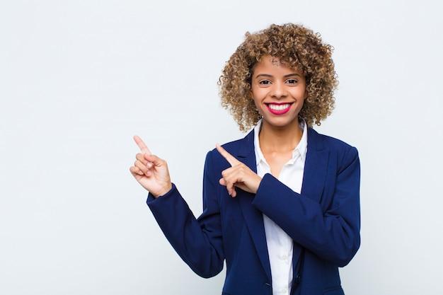 Afroamerikaner der jungen frau, die glücklich lächelt und zur seite und nach oben mit beiden händen zeigt, die objekt im kopienraum gegen flache wand zeigen