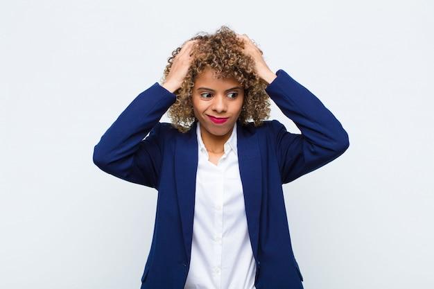 Afroamerikaner der jungen frau, die sich frustriert und genervt, krank und müde vom versagen fühlt, satt von langweiligen, langweiligen aufgaben über der mauer