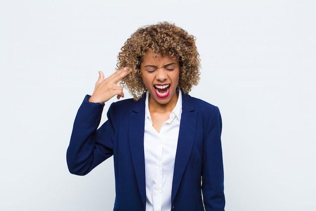 Afroamerikaner der jungen frau, die unglücklich und gestresst schaut, selbstmordgeste, die waffenzeichen mit hand macht, zeigt auf kopf gegen flache wand