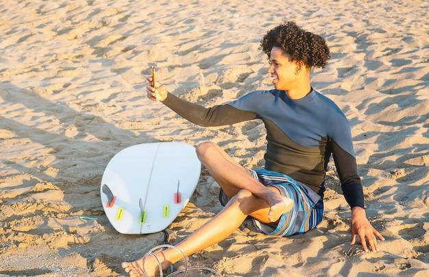 Afroamerikaner, der mit surfbrett im sand sitzt, macht ein foto mit einem smartphone